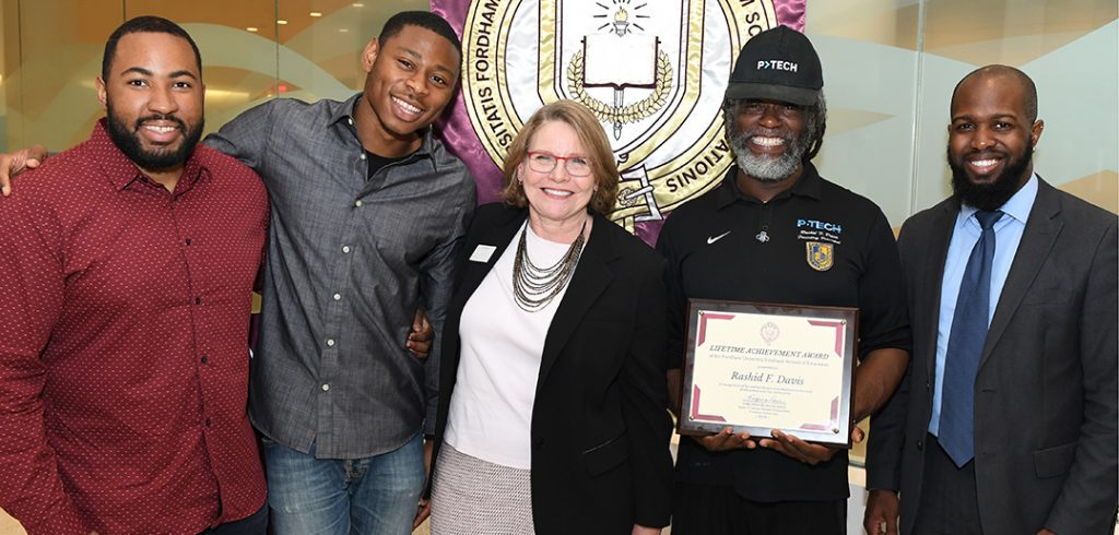 P-TECH staff and alumnus celebrate Rashid Davis's award, from left: Cordel Blair GSE '17, assistant principal; Radcliffe Saddler, recent graduate; GSE Dean Virginia Roach; Rashid Davis, GSE '03; and Victor John, assistant principal.