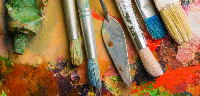 Paintbrushes lined up on painted surface