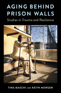 older black man sitting on prison bed with his hands perched on a walker
