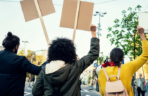 three people with signs and raised fists at a protest march