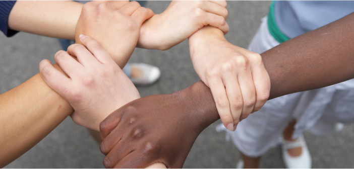 people of different races grabbing one another's wrists in unity