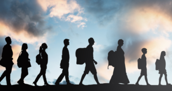 silhouettes of people walking in line with backpacks indicating immigration